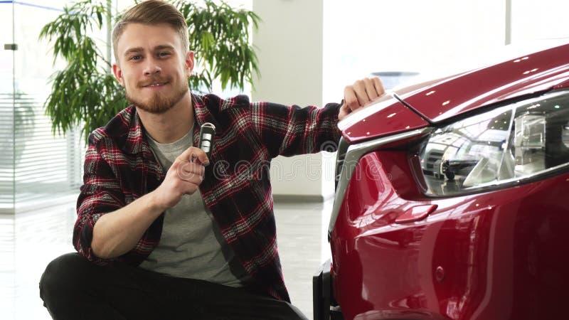 Homme bel heureux posant avec sa nouvelle automobile montrant des clés de voiture à l'appareil-photo photos libres de droits