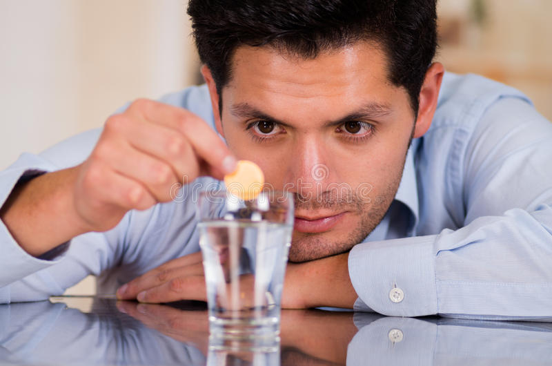 Homme bel laissant tomber le comprimé effervescent en verre de l'eau images libres de droits