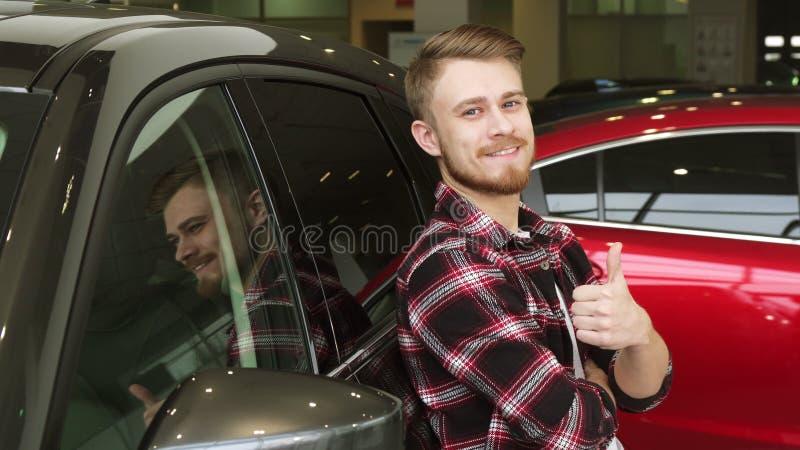 Homme bel montrant des pouces se penchant sur une nouvelle voiture au concessionnaire photo stock