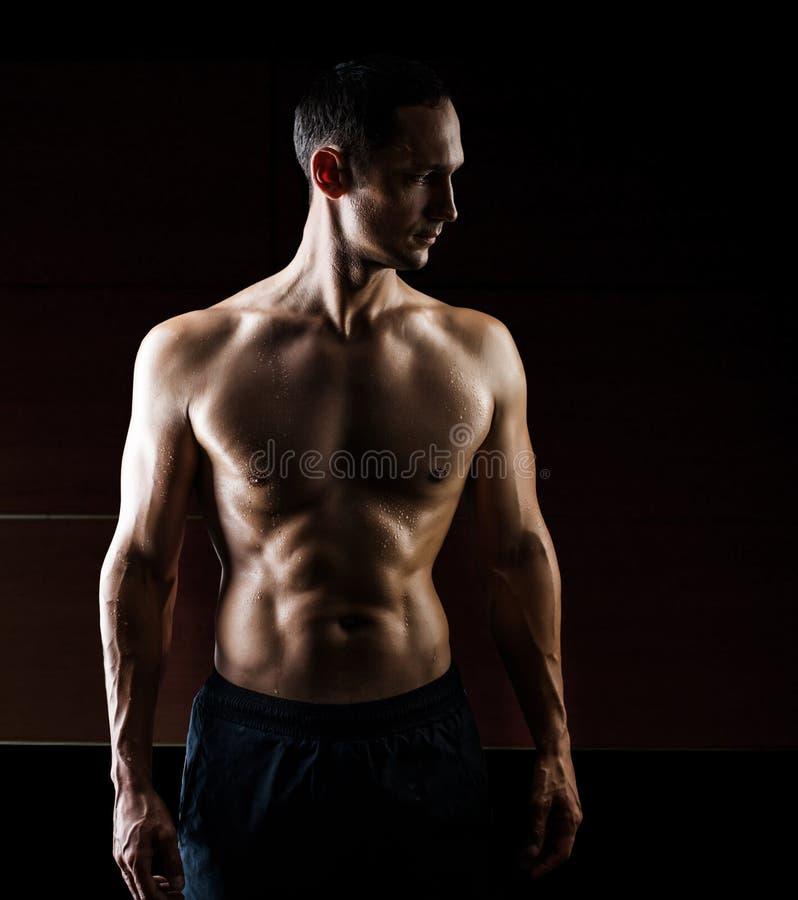 Homme bel musculaire d'isolement sur le fond noir images stock