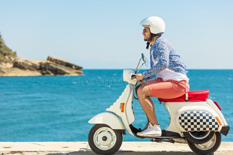 Homme bel posant sur un scooter dans un contexte de vacances Mode et style de rue photographie stock libre de droits