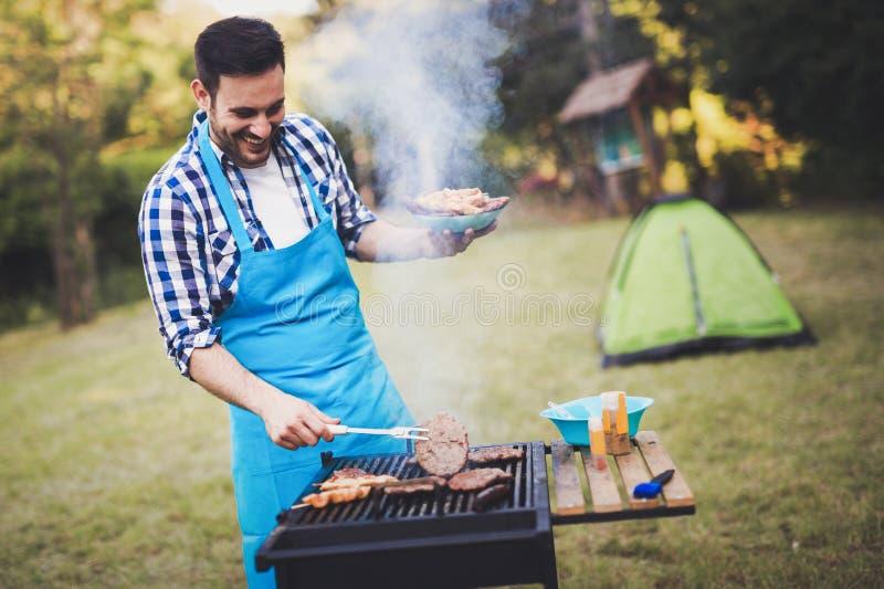 Homme bel préparant le barbecue image libre de droits