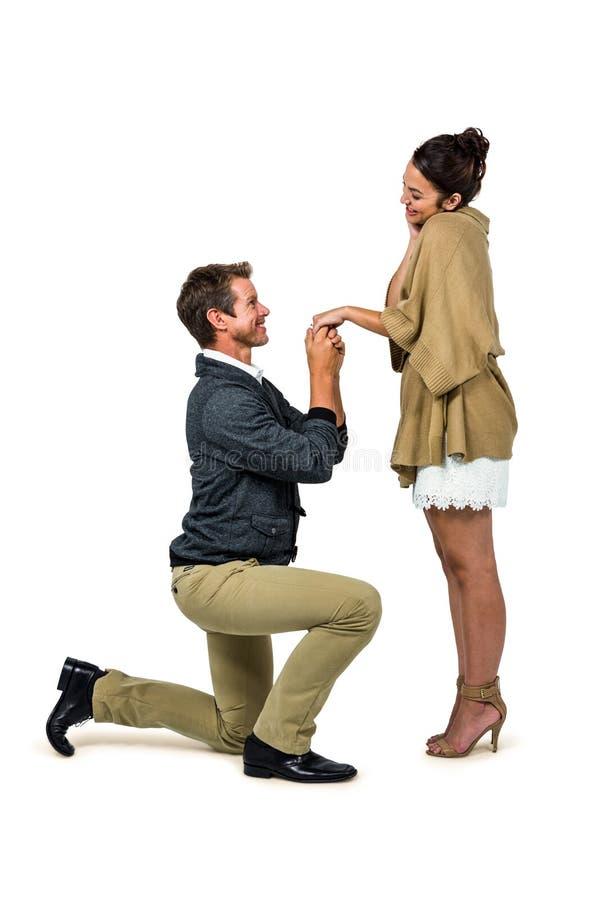 Homme bel proposant la belle femme tout en se mettant à genoux image stock