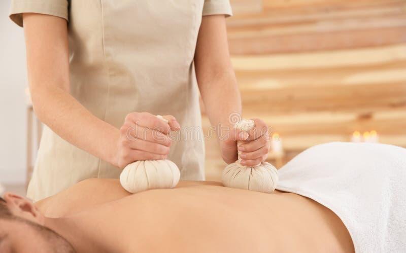 Homme bel recevant le massage de fines herbes de sac, plan rapproch? photos stock
