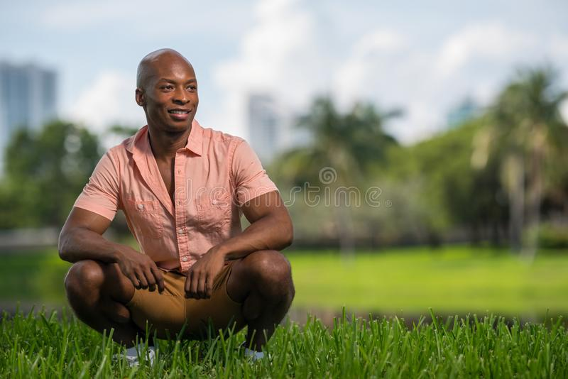 Homme bel regardant la caméra et le sourire Pose dans une posture accroupie en parc avec le fond trouble photo stock