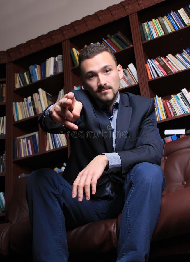 Homme bel respectable à côté d'une étagère images stock