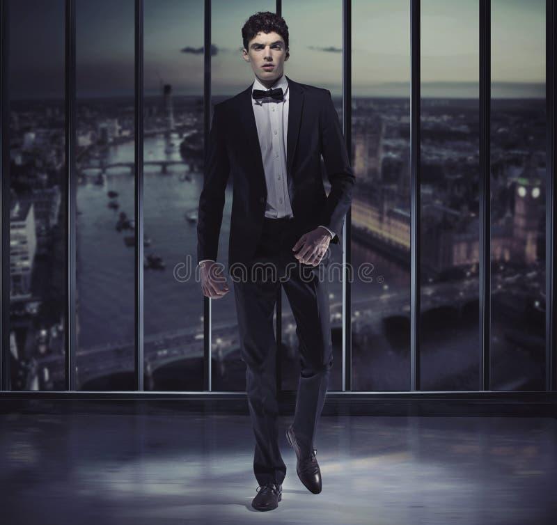 Homme bel sérieux sur le dessus du gratte-ciel photo stock