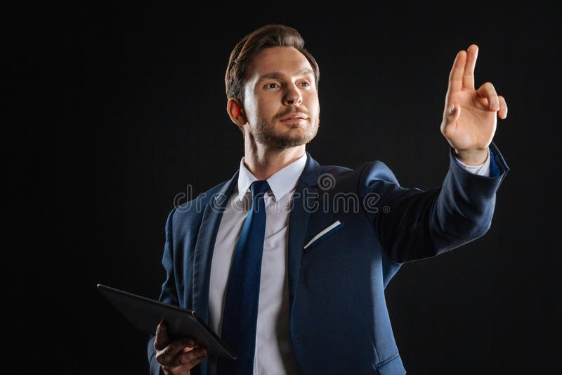 Homme bel sûr tenant le comprimé touchant à l'objet photographie stock