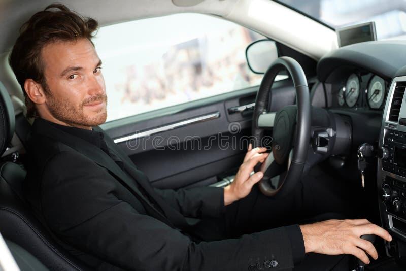 Homme bel s'asseyant dans la voiture photos stock