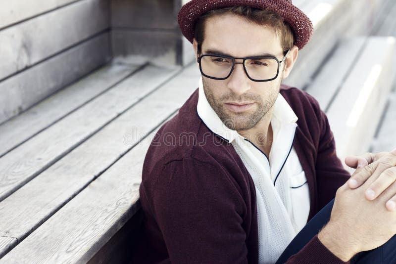 Homme bel s'asseyant dehors image stock