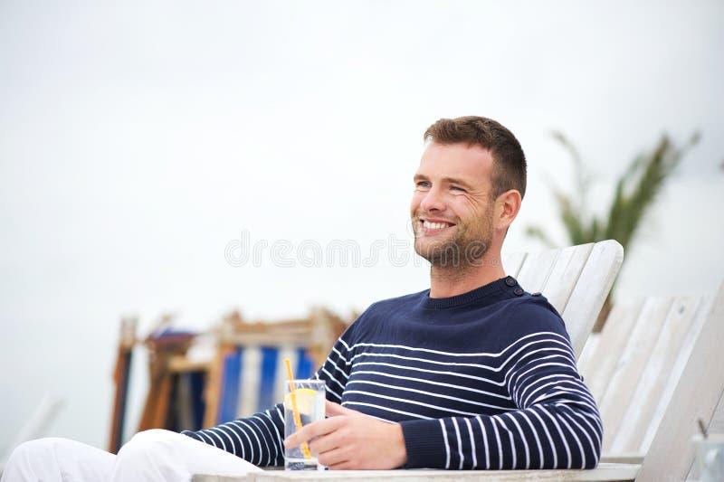 Homme bel s'asseyant et souriant à l'extérieur image stock