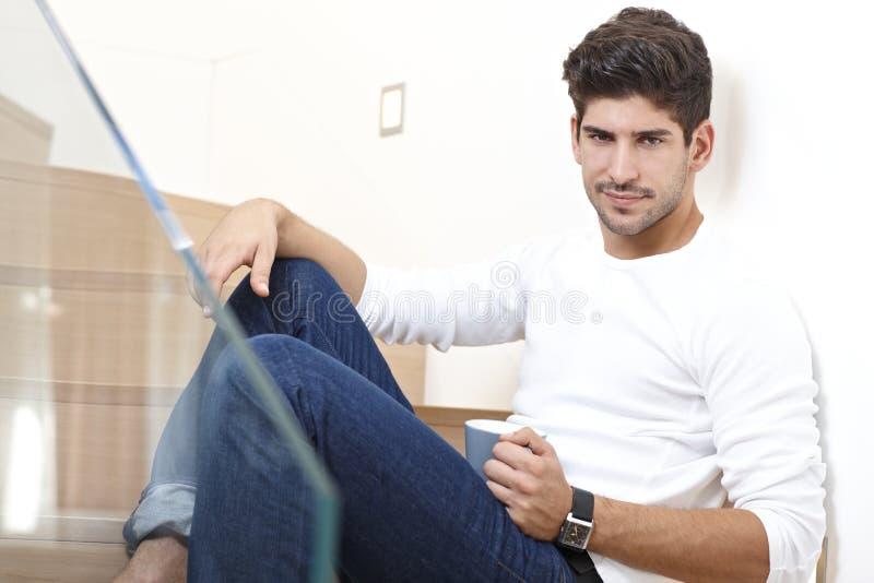 Homme bel s'asseyant sur des escaliers avec du café photos libres de droits