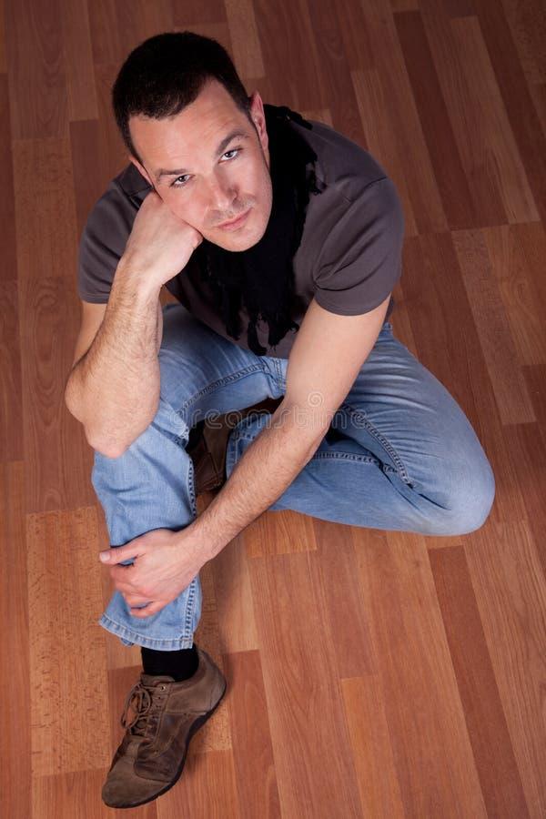 Homme bel, s'asseyant sur l'étage photos libres de droits