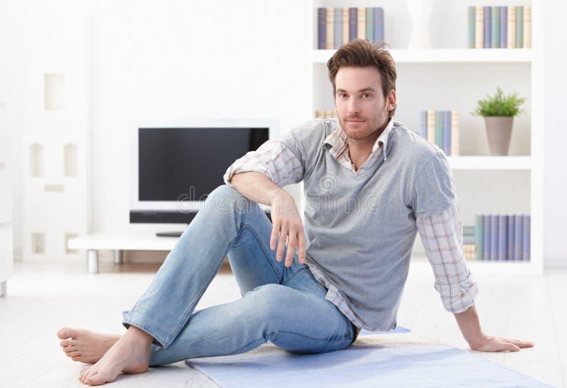 Homme bel s'asseyant sur l'étage de salle de séjour photo libre de droits