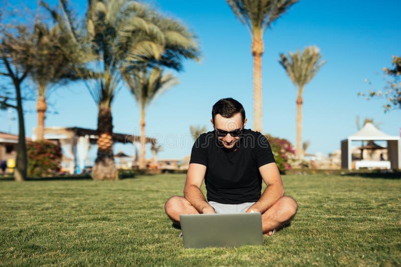 Homme bel s'asseyant sur l'herbe et l'ordinateur portable d'utilisation, chating ou actualités lues d'Internet sur le fond de pau image libre de droits