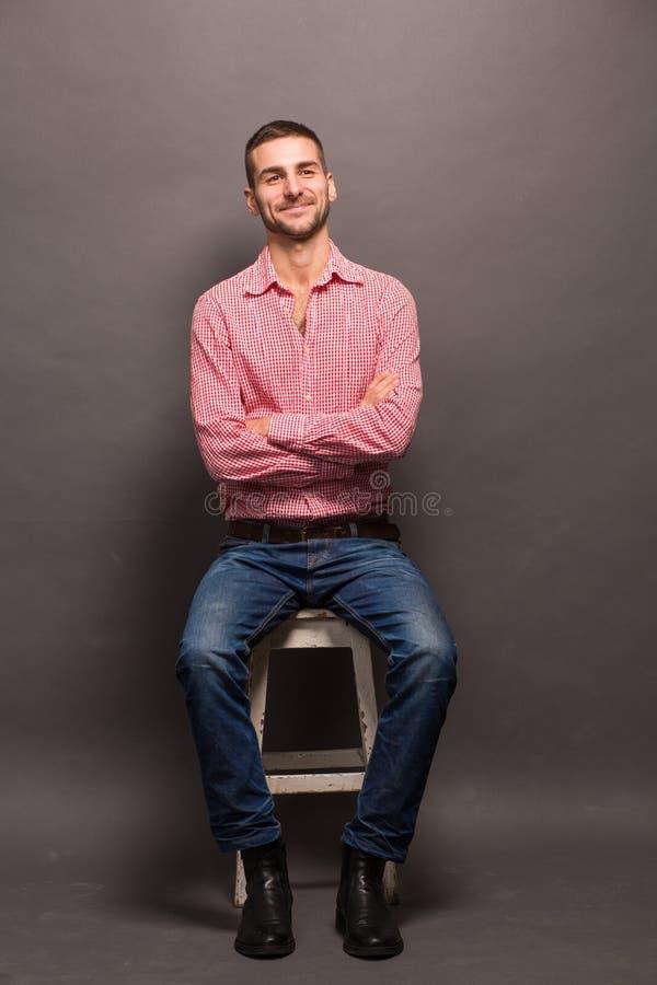 Homme bel s'asseyant sur une chaise dans le studio image stock