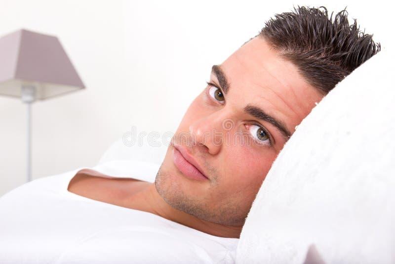 Homme bel se situant dans le lit photographie stock