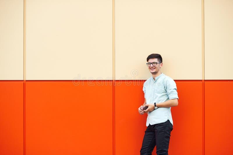 Homme bel souriant au-dessus d'un mur orange photographie stock