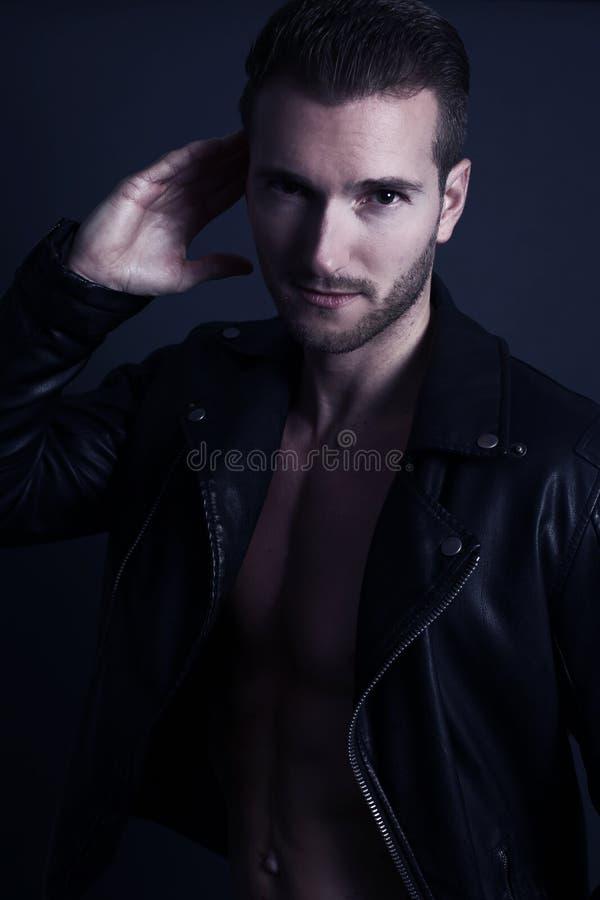 Homme bel utilisant une veste en cuir noire image libre de droits