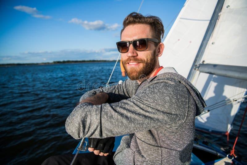 Homme bel voyageant en yacht Équipement occasionnel, homme habillé dans le hoodie gris, printemps, homme barbu dans des lunettes  photo libre de droits