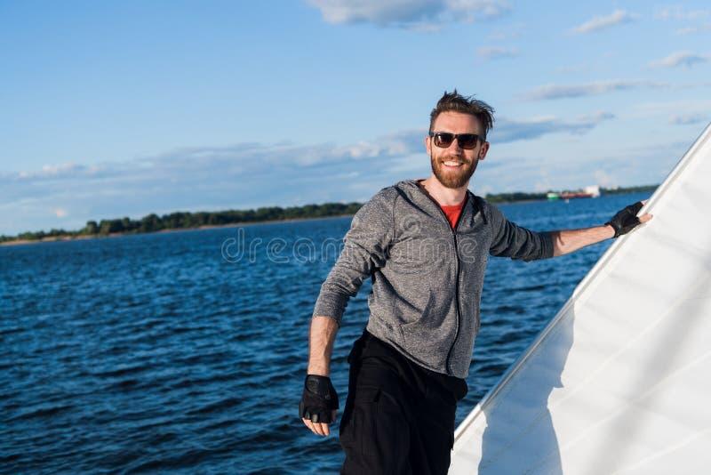 Homme bel voyageant en yacht Équipement occasionnel, homme habillé dans le hoodie gris, printemps, homme barbu dans des lunettes  photographie stock libre de droits