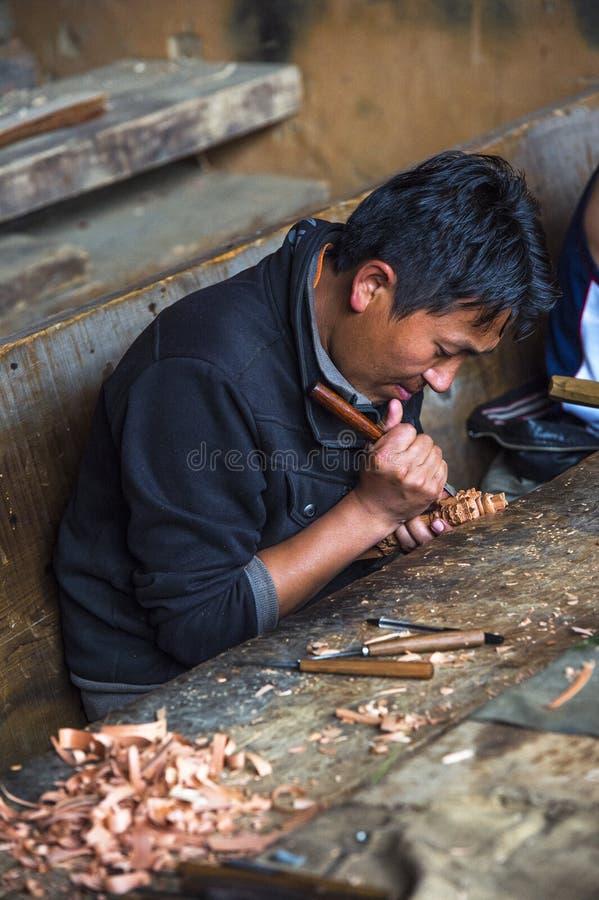 Homme bhoutanais de métier découpant le vajra, découpage du bois, Bhutan images libres de droits