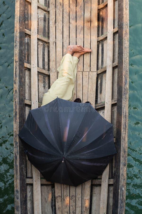 Homme birman dormant dans un bateau couvert de parapluie noir sur le lac Inle, Myanmar photo stock