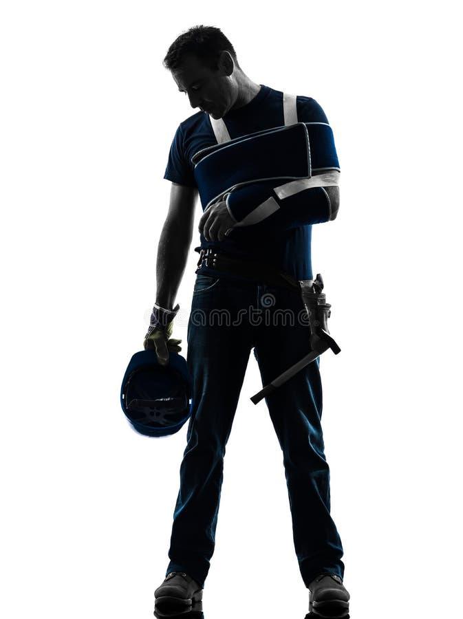 Homme blessé de travailleur manuel avec la silhouette de désespoir d'accolade de blessure photographie stock