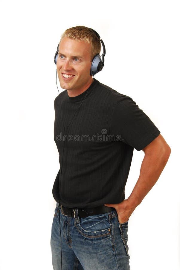 Homme blond écoutant la musique image stock