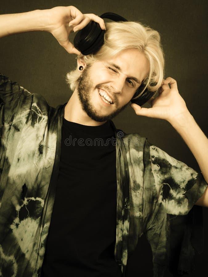Homme blond chantant dans des écouteurs de port de studio images stock