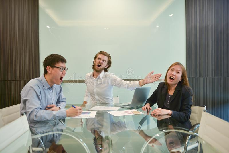 Homme blond d'affaires giflant l'employé asiatique dans le lieu de réunion photo libre de droits