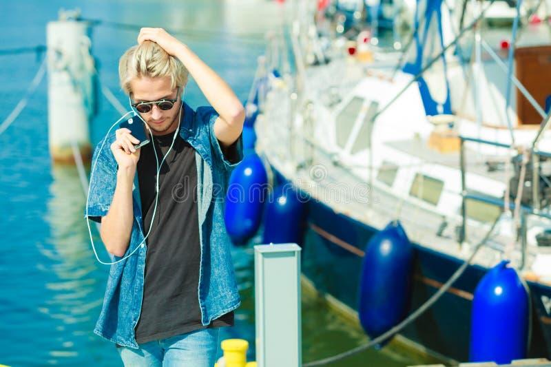 Homme blond dans des lunettes de soleil écoutant la musique image libre de droits