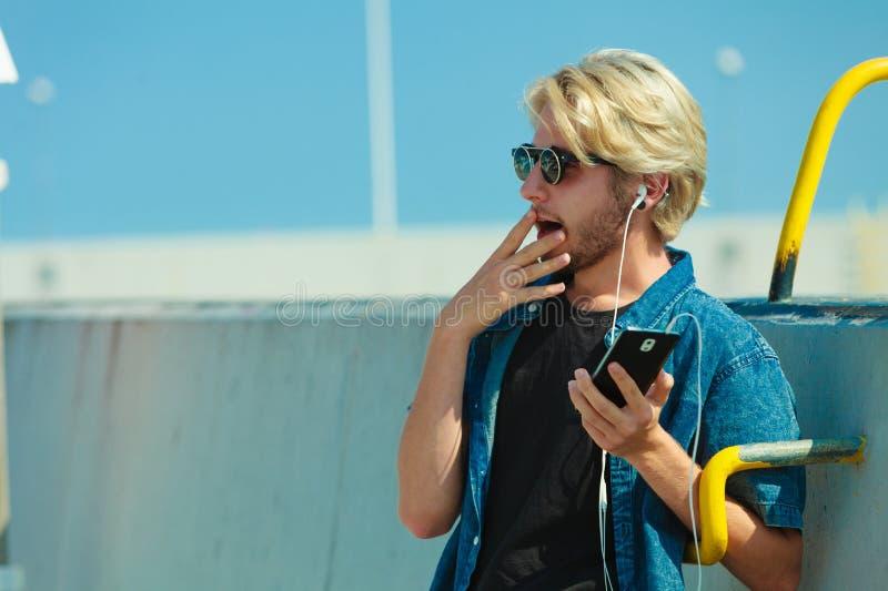 Homme blond dans des lunettes de soleil écoutant la musique images libres de droits