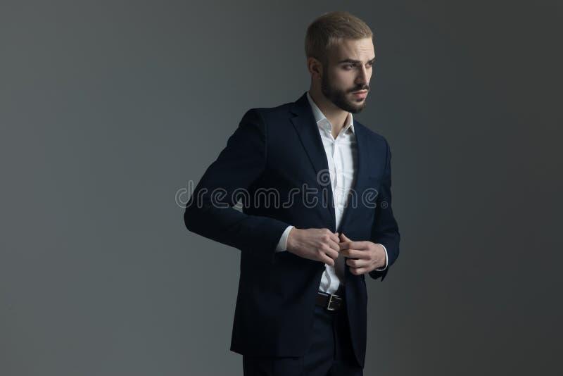 Homme blond dans le costume ajustant sa veste de salon images libres de droits