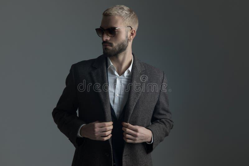 Homme blond dans le costume avec des lunettes de soleil ajustant son longcoat photographie stock