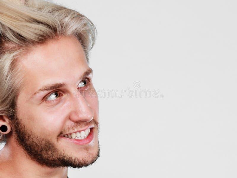 Homme blond de sourire heureux avec les cheveux ébouriffés par le vent photo stock