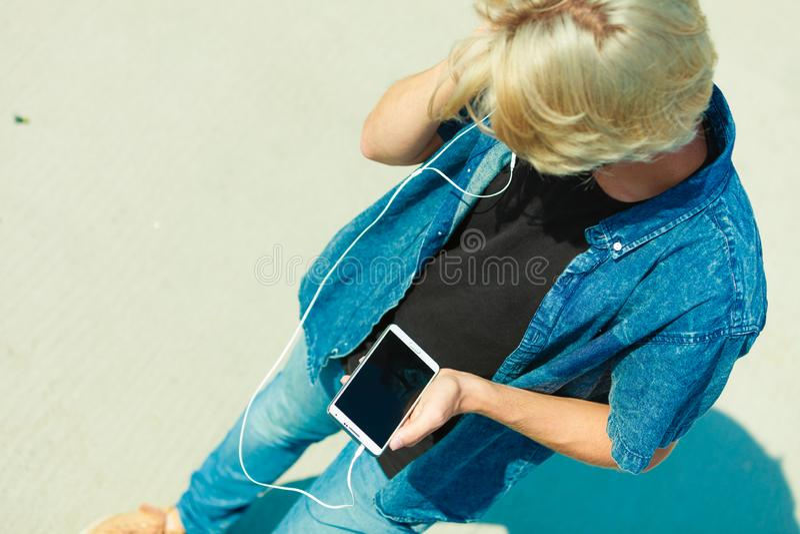 Homme blond dehors utilisant son smartphone images stock