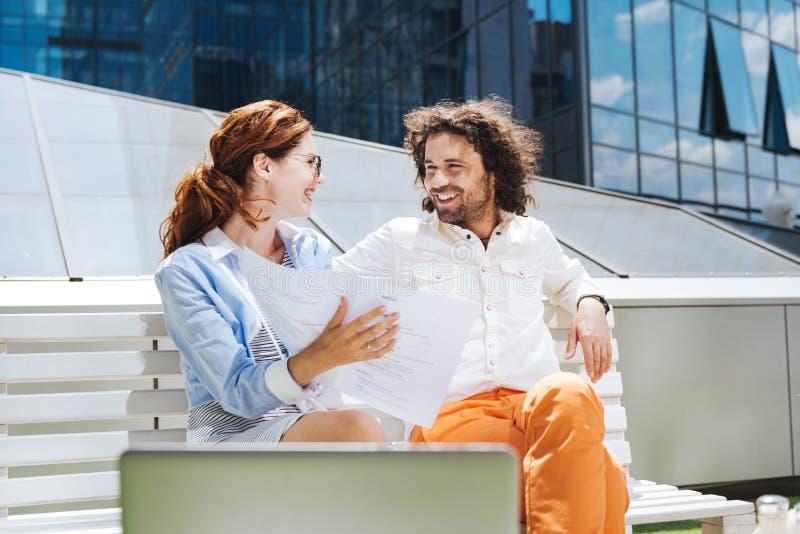 Homme bouclé barbu souriant tout en parlant à sa belle femme images stock