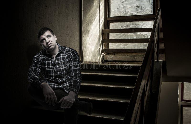 Jeune homme mécontent s'asseyant sur des escaliers images stock