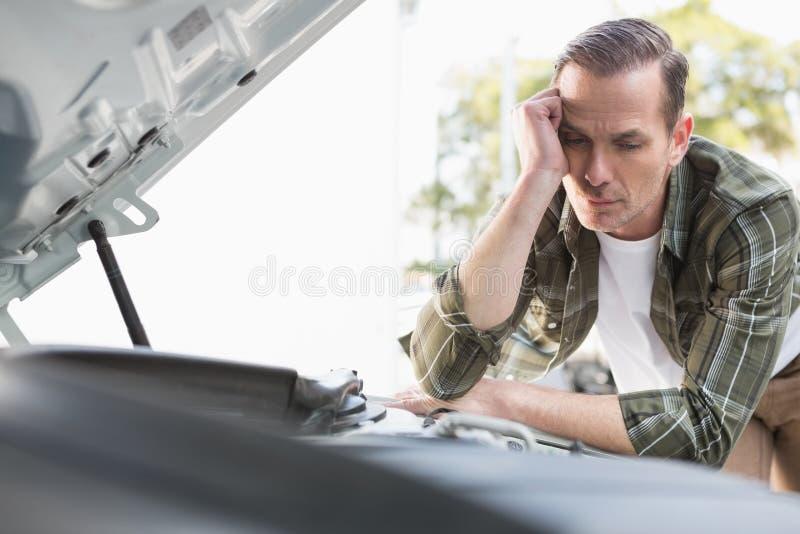 Homme bouleversé vérifiant son moteur de voiture après la décomposition photo stock