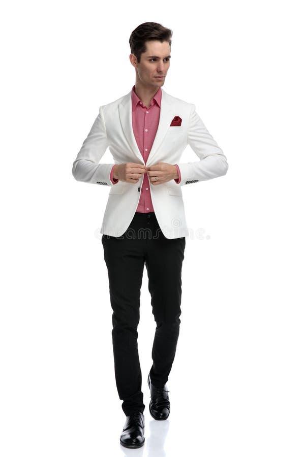 Homme boutonnant son manteau tandis que promenades et regards pour dégrossir photographie stock libre de droits