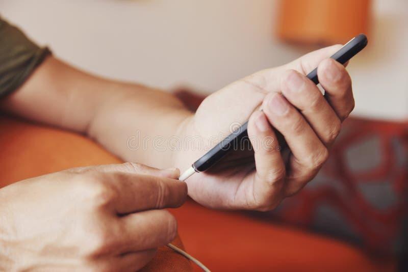 Homme branchant un câble à son smpartphone image libre de droits