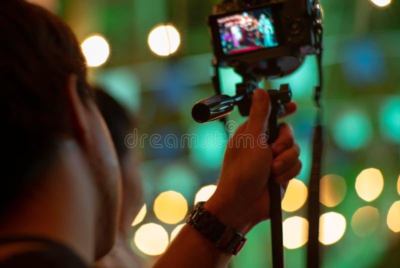 Homme brouillé de mouvement utilisant la caméra avec le trépied avec les lumières de scintillement de bokeh à l'arrière-plan Port images stock