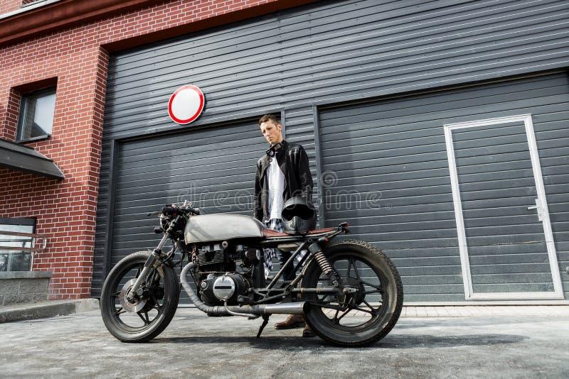Homme brutal près de sa motocyclette de coutume de coureur de café images libres de droits