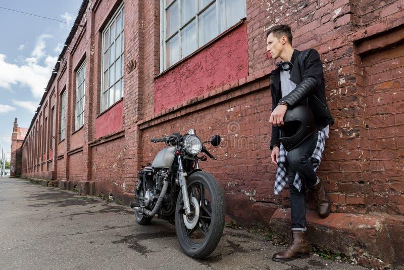 Homme brutal près de sa motocyclette de coutume de coureur de café photographie stock libre de droits