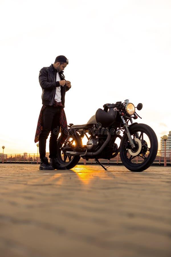 Homme brutal près de sa motocyclette de coutume de coureur de café image stock