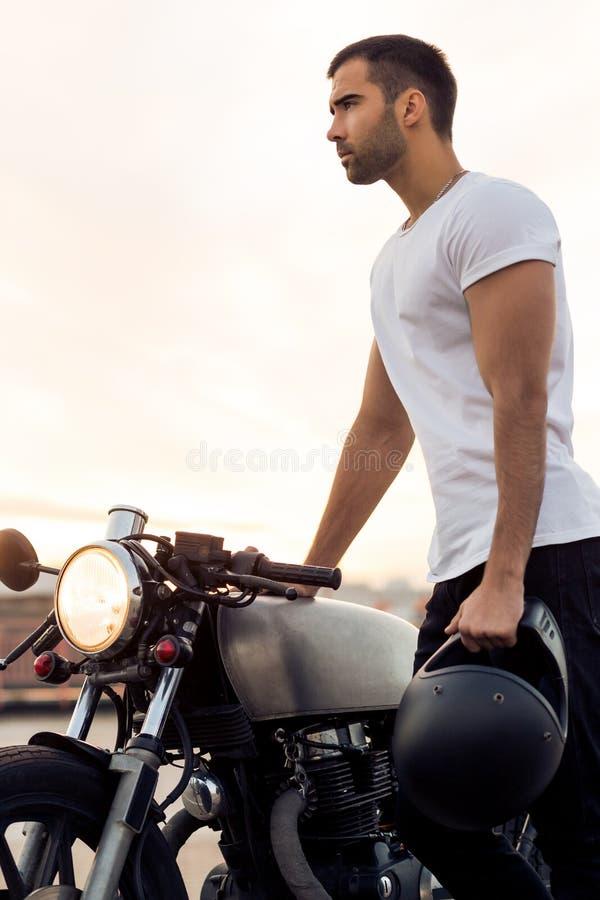 Homme brutal près de sa motocyclette de coutume de coureur de café photos libres de droits