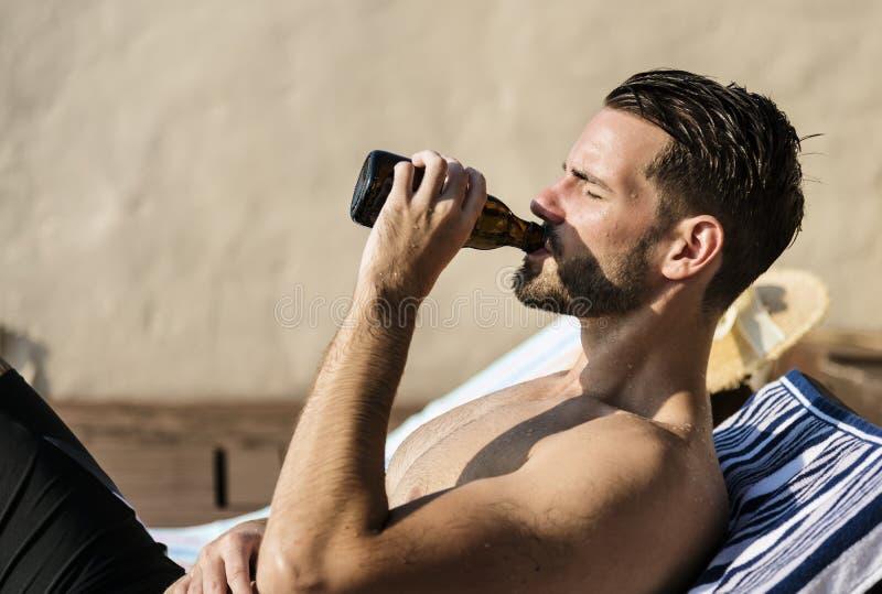 Homme buvant d'une bière par la piscine photographie stock libre de droits