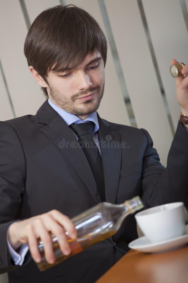 Homme buvant par le travail de bureau image stock