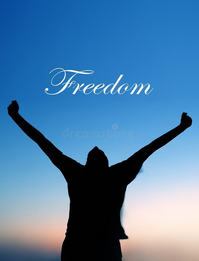 Homme célébrant au coucher du soleil avec le texte de liberté photos libres de droits